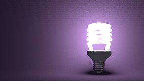 Glowing spiral light bulb on violet Royalty Free Stock Photos