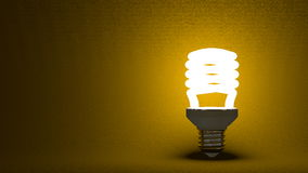 Glowing spiral light bulb on yellow Stock Photo