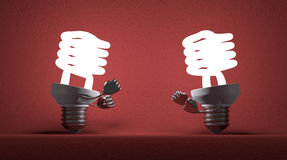 Glowing spiral light bulbs fighting with fists Stock Photos