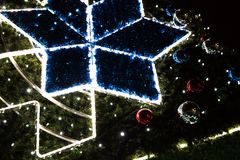 Glowing star and balls on Christmas tree, abstract Christmas background.  Royalty Free Stock Photography