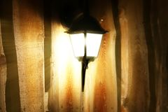 Glowing street lamp on the background of a wooden fence at night. Light permeates the darkness. Street lighting. Creating a cozy a royalty free stock photo