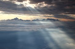 Glowing sun rays illuminate snowy Julian Alps and sea of clouds. Jagged Julian Alps range with Triglav and Skrlatica, highest peaks of Slovenia towers above Sava Royalty Free Stock Image