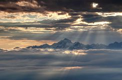 Glowing sun rays illuminate snowy Julian Alps and sea of clouds Royalty Free Stock Images