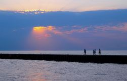 Glowing Sun Rays over the Lake. An unusually beautiful burst of gold and pink sun rays peer through evening clouds of blue. Silhouetted people walk along a pier stock images