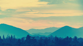 Glowing sun sets behind mountains. Royalty Free Stock Photos