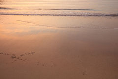 Glowing sunset in ocean. Sky reflecting in water and sand Royalty Free Stock Photography