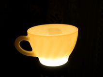 Glowing Tea Cup. Glowing ceramic cup isolated against a black background Royalty Free Stock Images