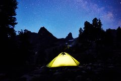 Glowing tent in the background of the night starry sky in the mo stock images