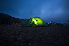 Glowing tent stands in camping Landmannalaugar, Iceland. Twilight, night. Royalty Free Stock Image