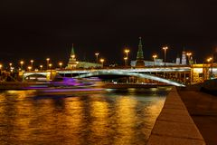 Glowing traces of pleasure boat on a background of Bolshoy Kamenny Bridge over Moskva river at night royalty free stock photos