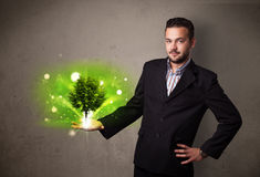 Glowing tree growing in the hand of a businessman Royalty Free Stock Photos