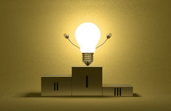 Glowing triumphant light bulb character on podium Stock Photo