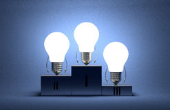 Glowing tungsten light bulb characters on podium Stock Photo