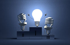 Glowing tungsten light bulb and dead spiral ones on podium Royalty Free Stock Images