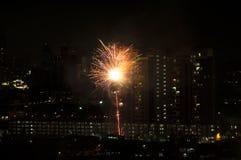 Sparkling firework bursting above Kuala Lumpur and Petaling Jaya (Malaysia). Glowing vivid sparkle of firework bursting above dark city in night. Originally royalty free stock images