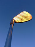 Glowing Wedge. A golf club held up against the blue sky, the evening light makes it glow Royalty Free Stock Image
