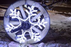 A glowing wheel, a Christmas garland in the shape of a snowflake on a wooden wheel of a cart. royalty free stock photo