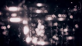 White blurred city lights with rain drops on glass loop background