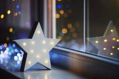 Glowing white LED star near window on warm bokeh background indoor. Festive Christmas illumination, holiday atmosphere stock photography