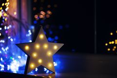 Glowing white LED star near window on warm bokeh background indoor at night. Festive Christmas illumination, holiday atmosphere royalty free stock photo