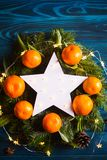 Glowing white LED star surrounded with fresh mandarins and spruce branches with garland lights. Closeup New Year festive card with fir royalty free stock photos