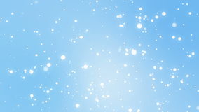 Glowing white snowflakes falling down against a light blue background royalty free illustration