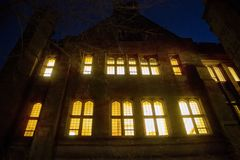 Glowing windows on a building at Yale University at night royalty free stock images
