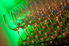 Glowing wine glasses. Barware wine glasses with green glowing light in background, lined up and ready to be filled Stock Photo