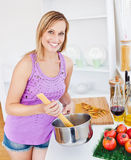 Glowing woman cooking spaghetti at home Stock Image