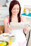 Glowing woman eating cereals and reading newspaper. Glowing woman eating cereals while reading newspaper in the kitchen at home Stock Images