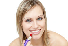 Glowing woman putting red lipstick Stock Images