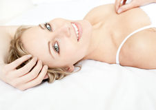 Glowing woman relaxing lying on her bed Stock Photo