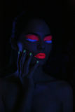 Glowing Woman Wearing UV Cosmetics Under Black Light Stock Image