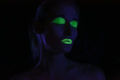 Glowing Woman Wearing UV Cosmetics Under Black Light Royalty Free Stock Image