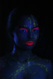 Glowing Woman Wearing UV Cosmetics Under Black Light Stock Photos