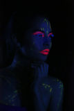 Glowing Woman Wearing UV Cosmetics Under Black Light Stock Images