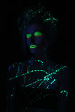 Glowing Woman Wearing UV Cosmetics Under Black Light Royalty Free Stock Photos