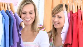 Glowing women choosing colorful shirts. Standing in a clothes shop stock video footage