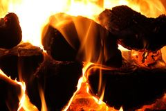 Glowing wood logs a fireplace. Warm fireplace - glowing wood logs and fire flames stock photo