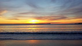 Glowing Yellow Sunrise over Ocean. Bright sunrise over the beach on a cloudy morning Royalty Free Stock Photography