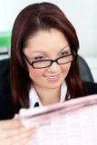 Glowing young businesswoman reading a newspaper Stock Images