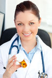Glowing young female doctor looking at pills Stock Photo