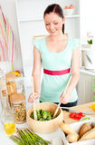 Glowing young woman preparing salad at home Royalty Free Stock Images