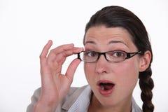 Gläser, die den Brunette überrascht tragen Lizenzfreie Stockfotos