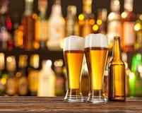 Gläser helles Bier mit Bar auf Hintergrund Stockfotos