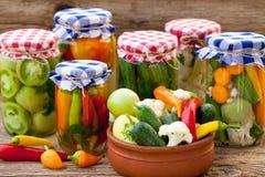 Gläser mit Essiggurken, Tomaten und Paprikas Lizenzfreie Stockfotos