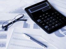 Gläser, Rechner und Feder auf Finanzdokumenten Lizenzfreies Stockfoto