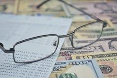 Gläser und Geschäftsbuch auf Dollarbanknote Stockfotos