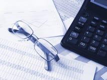 Gläser und Rechner auf Finanzdokumenten. Stockbild