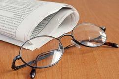 Gläser und Zeitung Stockfoto